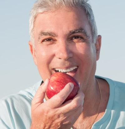 man eating an apple while wearing dentures