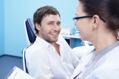 man with dentist discussing porcelain veneers