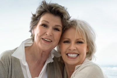 two senior woman smiling after getting dental bridges