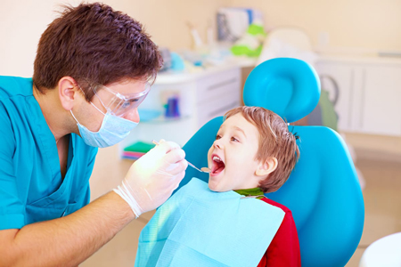 boy getting examined by dentist for spacers